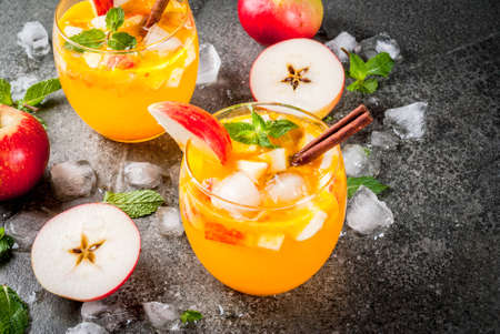 Traditional fall drinks, Apple cider mojito cocktails with mint, cinnamon and ice. On black stone table, copy space Stock Photo