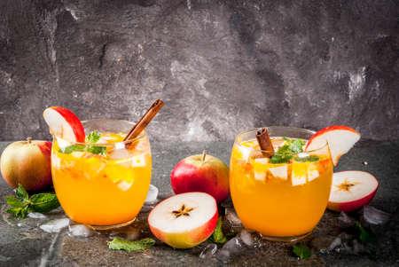伝統的な秋のドリンク、ミント、シナモン、氷をアップル サイダー モヒート カクテル。黒い石のテーブル スペースをコピーします。