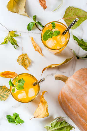 Fall and winter cold cocktails. Spicy pumpkin mojito with fresh mint, on white marble table. copy space top view