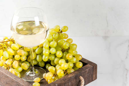 White grapes and white wine in a glass, in a wooden tray on a white marble table. Copy space
