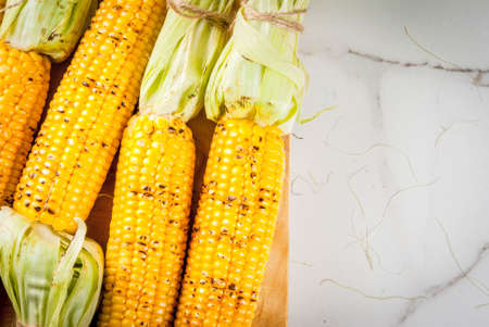 Autumn bbq, Grilled corn on white marble table, copy space Reklamní fotografie