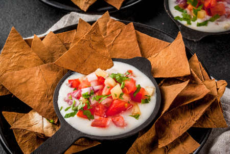 Mexican, LatinAmerican cuisine. Queso blanco recipe - cream cheese, cream, fresh stewed vegetables tomatoes, onions, peppers,  herbs. With Baked Tortilla Chips, black stone table.  copy space