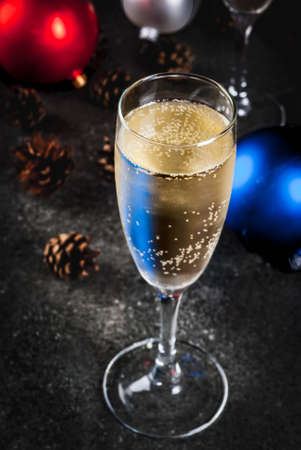 uncork: Dry Champagne in glasses, Christmas colorful balls, pine cones, New Year still life composition on dark stone background, selective focus copy space