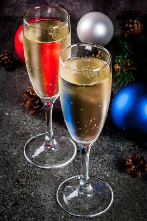 Champagne asciutto in bicchieri, palle colorate di Natale, coni di pino, composizione ancora di vita di nuovo anno su sfondo di pietra scura, fuoco selettivo copia spazio Archivio Fotografico - 84575210