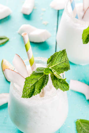 Summer refreshment drinks, cocktails. Frozen coconut mojito with lime and mint. Pina colada. On a light blue green wooden table with ingredients. Copy space close view Stock Photo