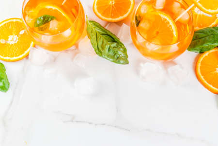 Summer refreshing drink, lemonade, cocktail with orange and basil. On a white marble table, copy space top view