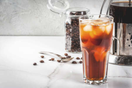 Trendy drinks. Cold brew iced coffee on white marble table. copy space