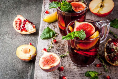 Warming autumn, winter cocktail drinks recipes. Hot red fruit sangria with apples, plums, figs, pomegranate, mint, cinnamon, thyme, lemon. On dark stone table, with wooden cutting board, copy space
