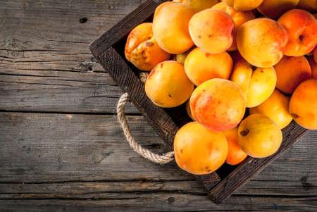 여름 과일입니다. 나무 상자, 오래 된 목조 소박한 테이블에 트레이에서 원시 신선한 유기농 팜 살구. 공간 위쪽보기 복사