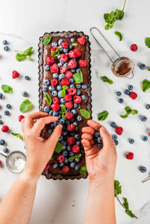 Summer homemade baked pastry. Chocolate cake tart with chocolate cream, woman decorate it with blueberry raspberry mint leaves, powdered sugar. White marble table, copy space top view hands in picture