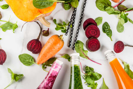 Vegan diet food. Selection colorful fresh organic smoothies drinks with autumn vegetables: beetroot, pumpkin, carrot, leafy vegetables. In bottles, white table. Copy space top view