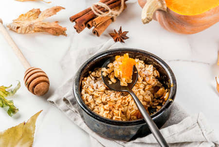 Dietary autumn pastries, breakfast. Crumble pumpkin pie, maple syrup and oatmeal flakes, in plate saucers, on a white marble table. Copy space Stock Photo - 84981580