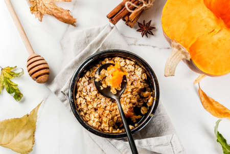 Dietary autumn pastries, breakfast. Crumble pumpkin pie, maple syrup and oatmeal flakes, in plate saucers, on a white marble table. Copy space