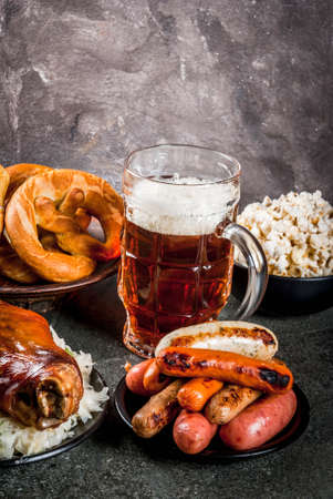 Selection of traditional German food Oktoberfest. Beer, baked pork shank, popcorn, assortment of different sausages, homemade bretzels. On a black stone background copy space