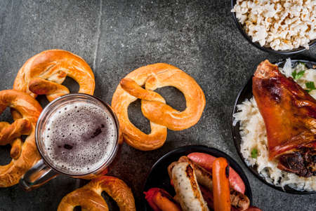 Selection of traditional German food Oktoberfest. Beer, baked pork shank, popcorn, assortment of different sausages, homemade bretzels. On a black stone background copy space top viwe Stock Photo