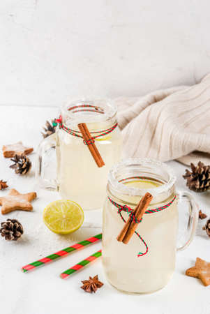 Fall and winter drinks. Christmas holiday beverage. Festive Snowball Cocktail with lime juice, cinnamon, liqueur, sugar and anise stars. On white table with christmas decoration, copy space