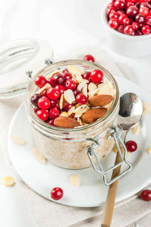 Recipe for a healthy winter breakfast, ideas for Christmas morning. Overnight oatmeal with almonds, cranberries, sugar. On a white marble table. copy space