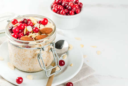Recipe for a healthy winter breakfast, ideas for Christmas morning. Overnight oatmeal with almonds, cranberries, sugar. On a white marble table. copy space Zdjęcie Seryjne - 85196193
