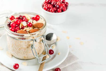 Ricetta per una sana colazione invernale, idee per la mattina di Natale. Farina d'avena durante la notte con mandorle, mirtilli rossi, zucchero. Su un tavolo di marmo bianco. copia spazio Archivio Fotografico - 85196193