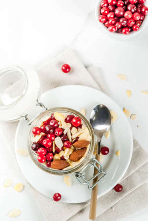 Recipe for a healthy winter breakfast, ideas for Christmas morning. Overnight oatmeal with almonds, cranberries, sugar. On a white marble table. copy space top view Stock Photo