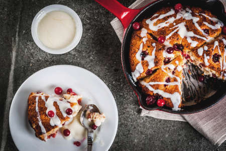 British English traditional pastries. Cookies pie cranberry scones with orange peel, with sweet white glaze, in a frying pan and on a plate. Black stone table, copy space top view 스톡 콘텐츠