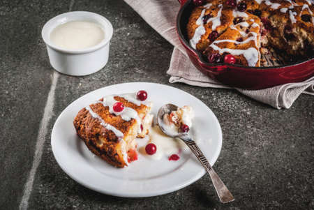 British English traditional pastries. Cookies pie cranberry scones with orange peel, with sweet white glaze, in a frying pan and on a plate. Black stone table, copy space