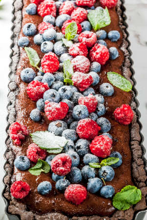 Summer homemade baked pastry. Chocolate cake tart with chocolate cream, fresh raw berries blueberry raspberry, decorated with mint leaves, powdered sugar. On white marble table, copy space close view Stock Photo