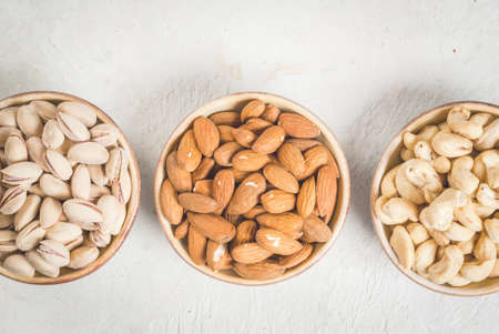 Selection nuts on a white stone table, in a bowl and scattered: almond, cashew and pistachio. Copy space top view