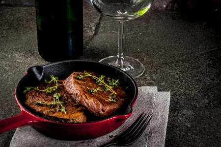 Lunch for one person. Homemade grilled beef steaks with thyme in a portioned frying pan, with a fork, knife and a glass of wine.  On black stone table, copy space