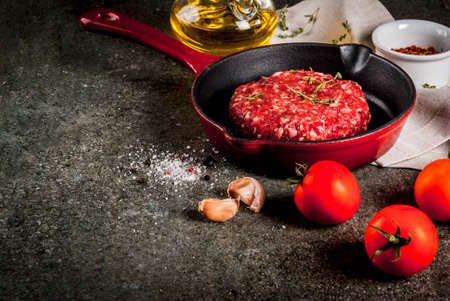Raw organic beef meat burgers cutlets  with spices, thyme, tomatoes, olive oil in frying pan on black background, copy space