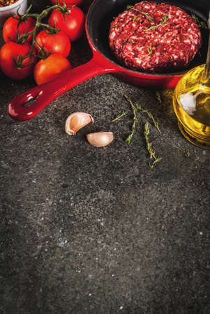 Raw organic beef meat burgers cutlets  with spices, thyme, tomatoes, olive oil in frying pan on black background, copy space top view
