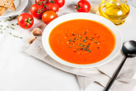 Tomato soup with olive oil and herbs, with toasted bread, on white marble background, copy space