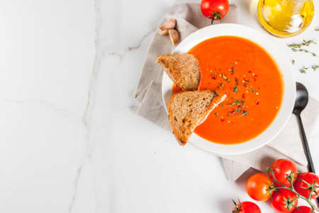 Tomato cream soup with olive oil and herbs, with toasted bread, on white marble background, copy space top view