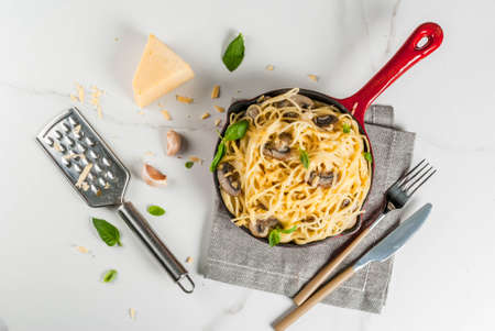 Creamy mushroom pasta with cheese and basil, in portioned frying pan, on white marble table, copy space top view Stock Photo