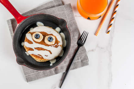 Funny food for Halloween. Kids breakfast pancake decorated like mummy with white chocolate sauce, banana, berries, with pumpkin smoothie juice, white table copy space top view 스톡 콘텐츠