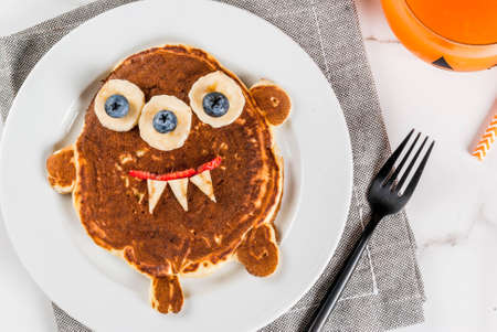 Funny food for Halloween. Kids breakfast pancake decorated like creepy monster, with banana, berries, with pumpkin smoothie juice, white table copy space top view