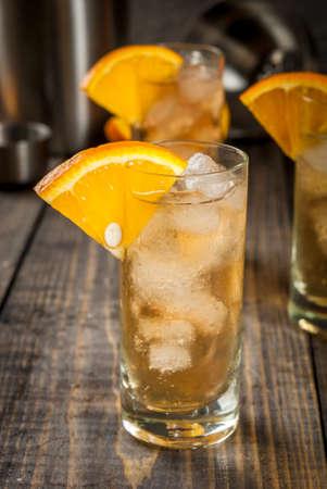 Cocktail alcolico alcolico di whisky alcolico con un goccio arancione, su un tavolo di legno copia spazio Archivio Fotografico