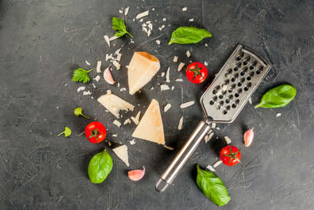 Ingredients of Italian cuisine.Parmesan grated and a piece, with a grater, basil leaves, garlic and cherry tomatoes on a dark concrete table. Top view copy space