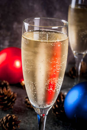 Dry Champagne in glasses, Christmas colorful balls, pine cones, New Year still life composition on dark stone background, selective focus copy space