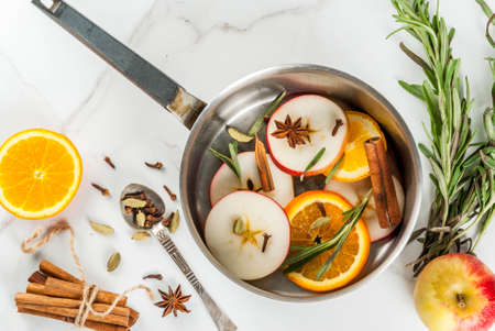 atmosphere: Traditional winter and christmas beverage, ingredients for mulled wine hot drink with citrus, apple and spices in aluminum casserole on white marble table. copy space top view
