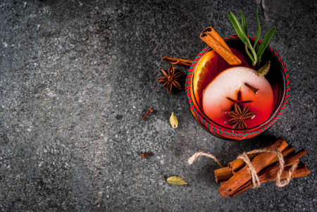 atmosphere: Traditional winter and autumn drinks. Christmas and Thanksgiving Cocktails. Mulled wine with orange, apple, rosemary, cinnamon and spices on a dark stone background, copy space top view Stock Photo