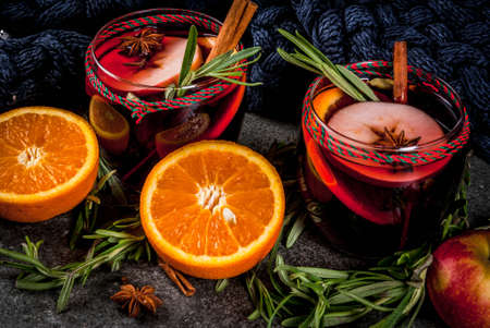 Traditional winter and autumn drinks. Christmas and Thanksgiving Cocktails. Mulled wine with orange, apple, rosemary, cinnamon and spices on a dark stone background, copy space Lizenzfreie Bilder
