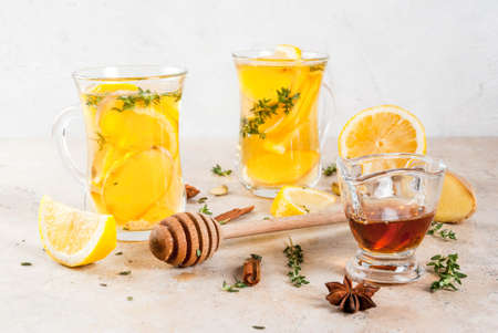 Fall and winter traditional drinks. Warming hot tea with lemon, ginger, spices (anise, cinnamon) and herbs (thyme), copy space