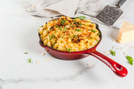 Mac e formaggio, pasta di macaroni in stile americano con salsa formaggi e croccanti di pane tostato, in casseruola, tavola di marmo bianco, copia spazio