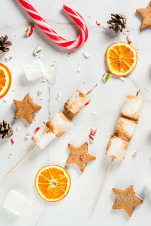 Traditional christmas sweets - candy cane, marshmallow, dried orange, gingerbread stars, baked on fire marshmallow skewers on white marble background, copy space top view Lizenzfreie Bilder