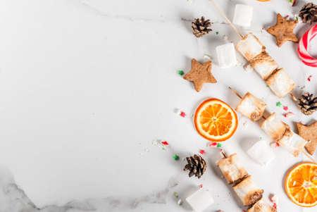 Dolci naturali tradizionali - canna di caramella, marshmallow, arancia secca, stelle di pan di zenzero, cotto al fuoco spuntini marshmallow su fondo marmo bianco, copia spazio vista dall'alto