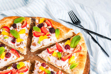 Summer snacks. Food for party. Fruit pizza with cream, currants, yogurt, strawberries, mango, peaches, bananas, blackberries, chocolate, walnuts, mint. On light blue table. Copy space