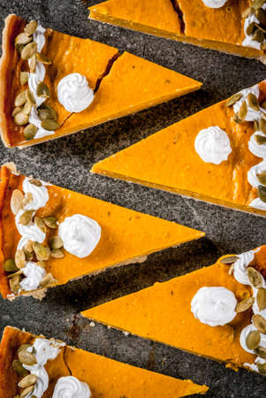 Traditional autumn dishes. Halloween, Thanksgiving. Set of cuted pieces of spicy pumpkin pie with whipped cream & pumpkin seeds on black stone table. Top view