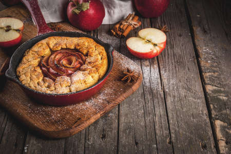 Traditional autumn baking, recipes for thanksgiving, Homemade wholegrain apple galette pie with organic apples and cinnamon, In iron cast pan, old wooden table, copy space