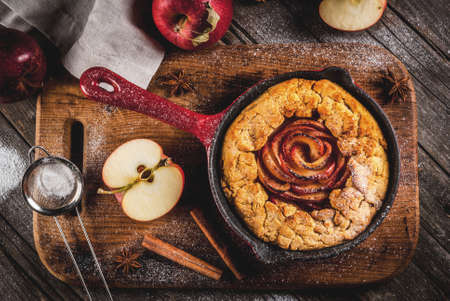 Traditional autumn baking, recipes for thanksgiving, Homemade wholegrain apple galette pie with organic apples and cinnamon, In iron cast pan, old wooden table, copy space top view